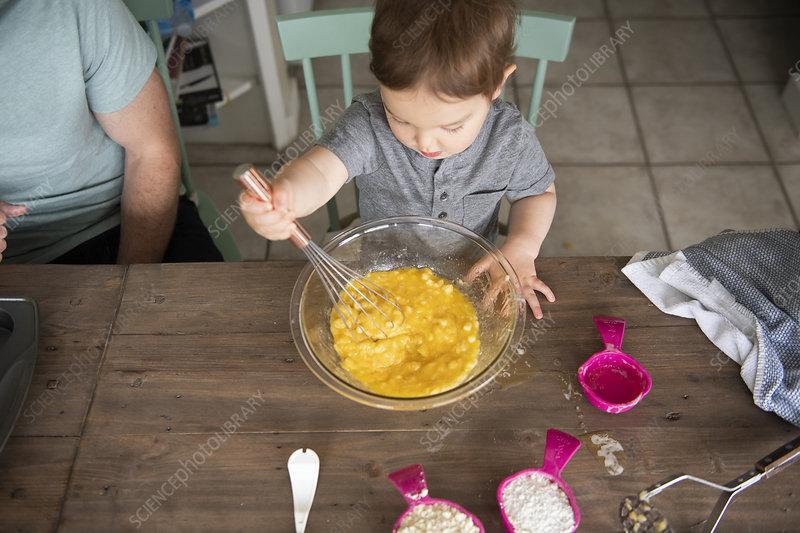 Curious toddler girl baking
