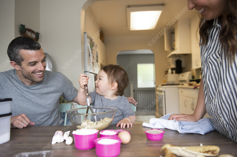 Happy young family baking at kitchen table