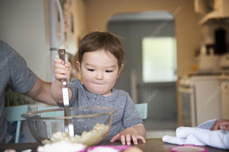 Cute toddler girl baking