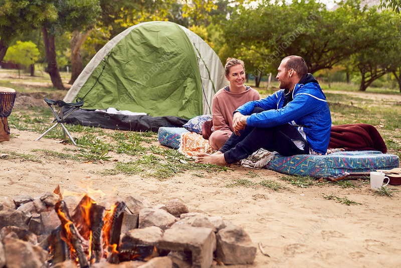 Young couple camping talking at campsite
