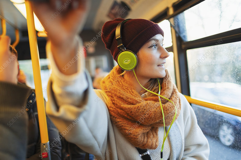 Woman listening to music with headphones on bus
