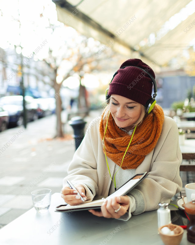 Woman with headphones writing in journal