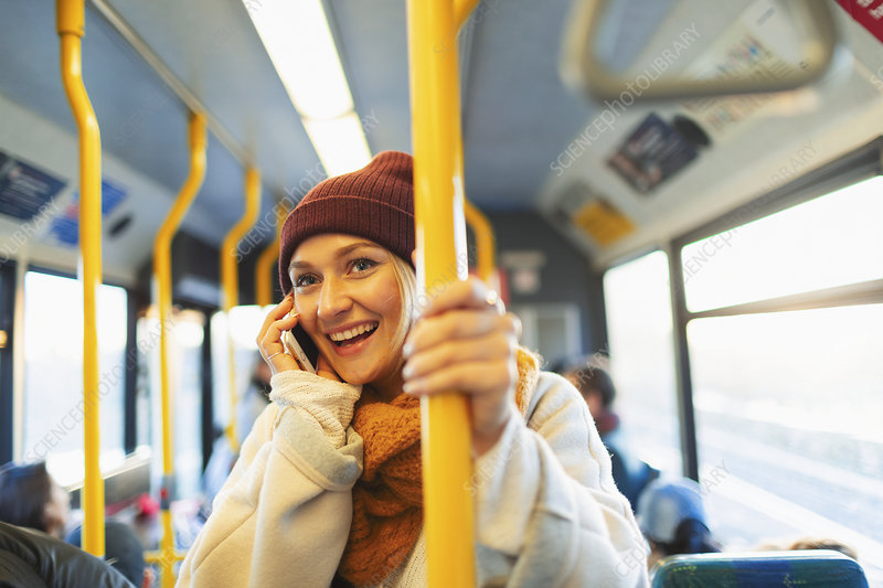 Woman talking on smart phone on bus
