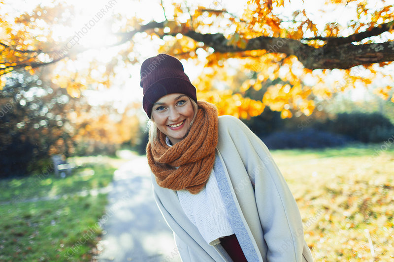 Woman in stocking cap and scarf in autumn park
