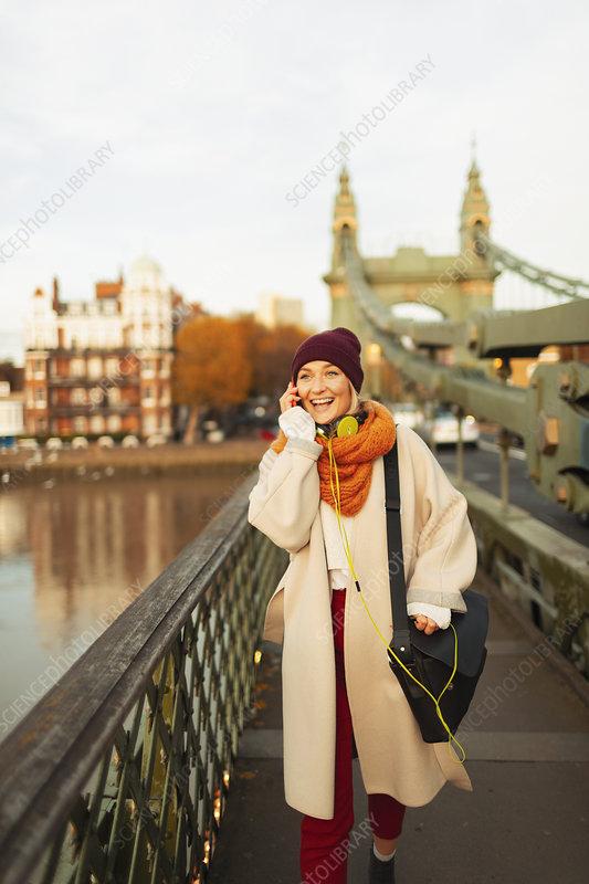 Woman talking on smart phone on urban bridge