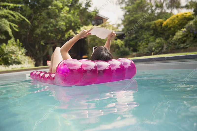 Woman reading book on inflatable raft