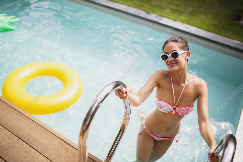 Woman in bikini getting out of summer swimming pool