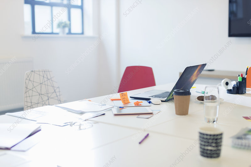 Laptop, paperwork and coffee on conference table