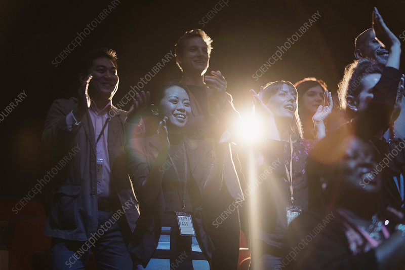 Happy audience clapping in dark room