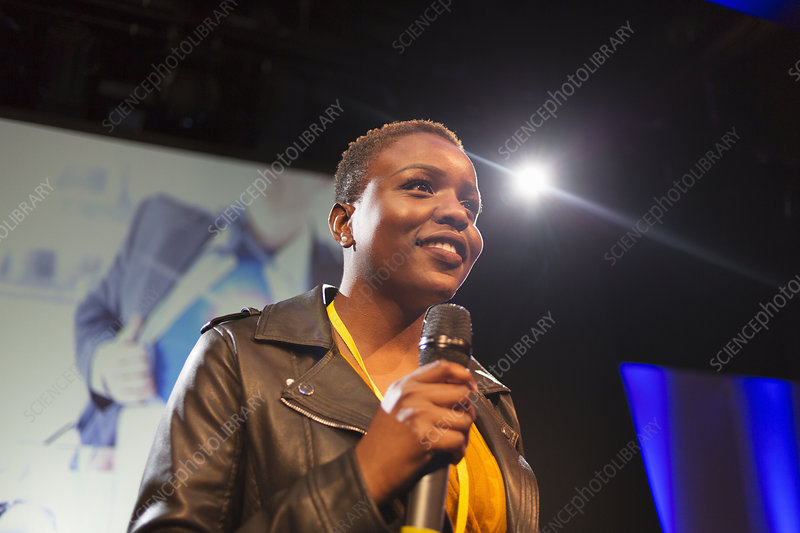 Smiling female speaker with microphone on stage