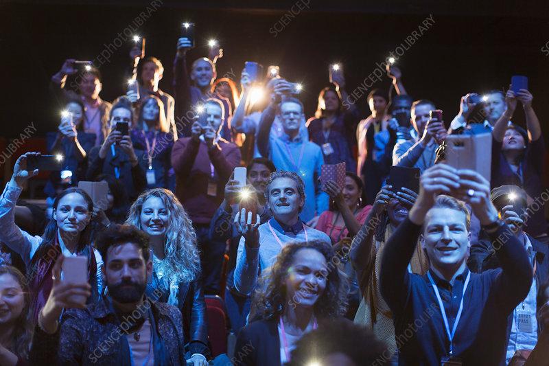 Audience with smart phone flashlights in dark auditorium