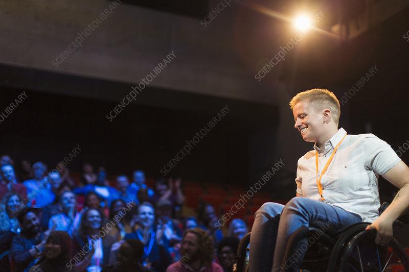 Smiling female speaker in wheelchair on stage
