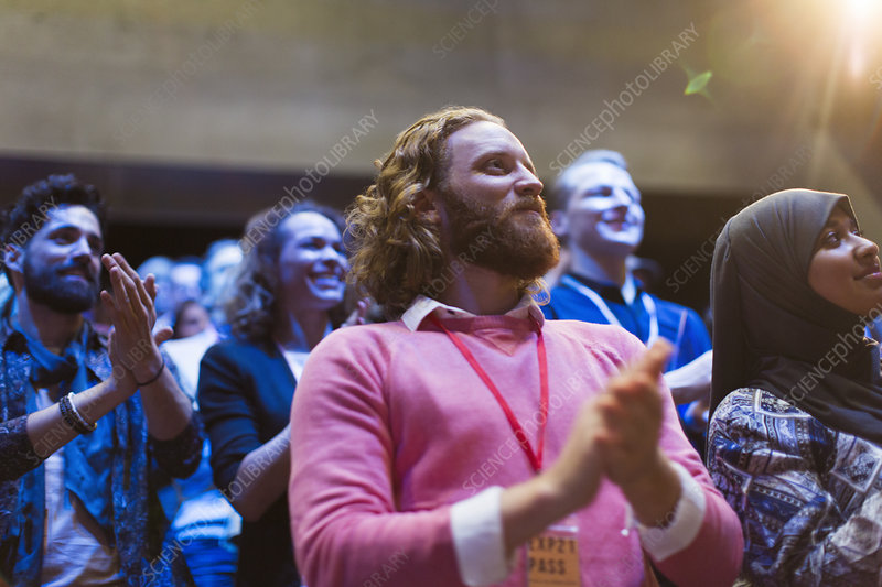 Smiling man clapping in audience