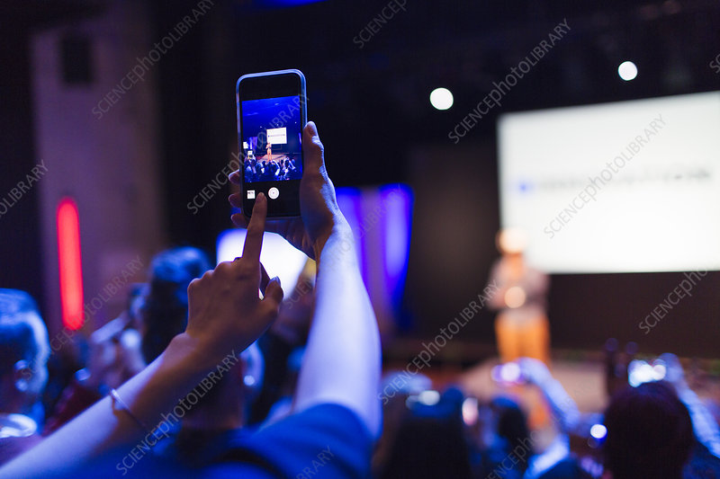 Woman photographing conference presentation