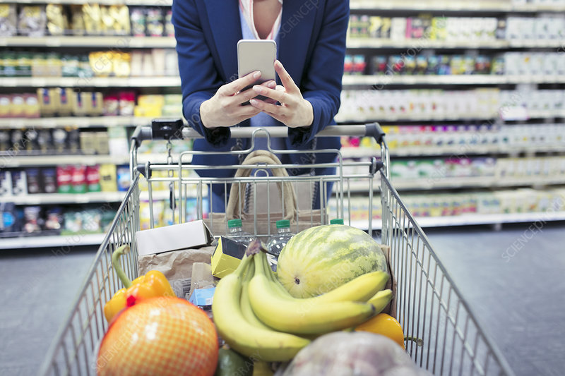 Woman with smart phone pushing shopping cart in supermarket