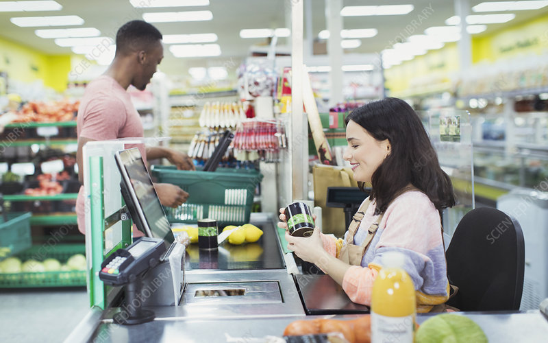 Cashier helping customer at supermarket checkout