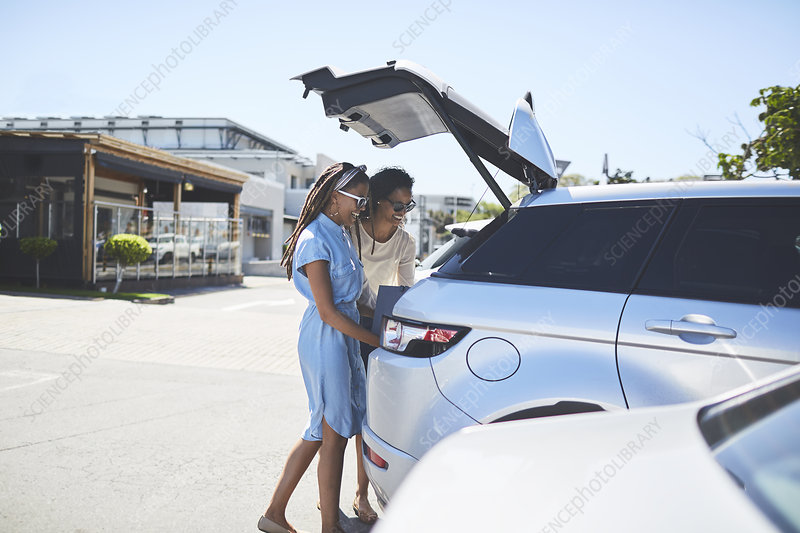 Women loading shopping bags into back of car