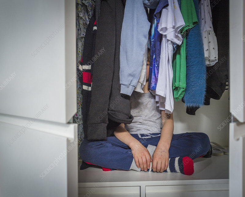Girl hiding in the closet stock photo. Image of light