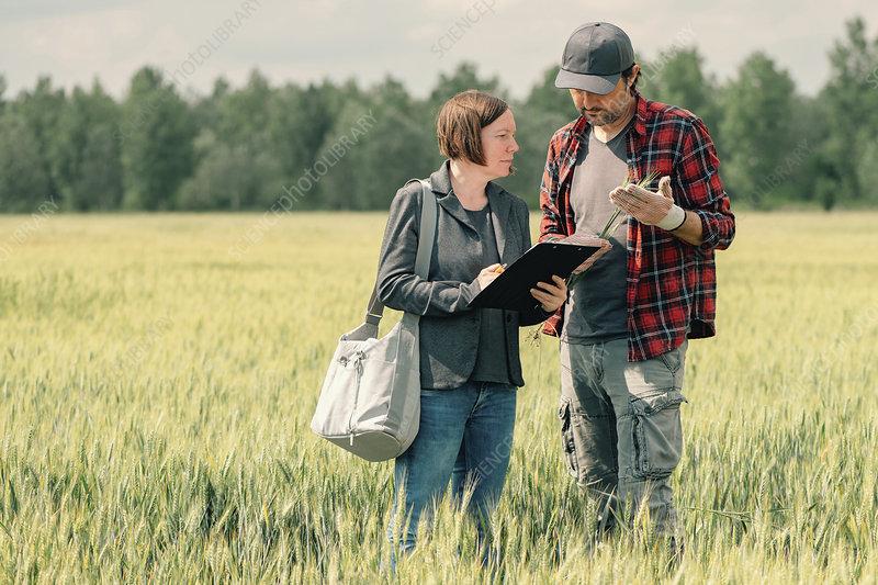 Mortgage loan officer assisting farmer in loan application