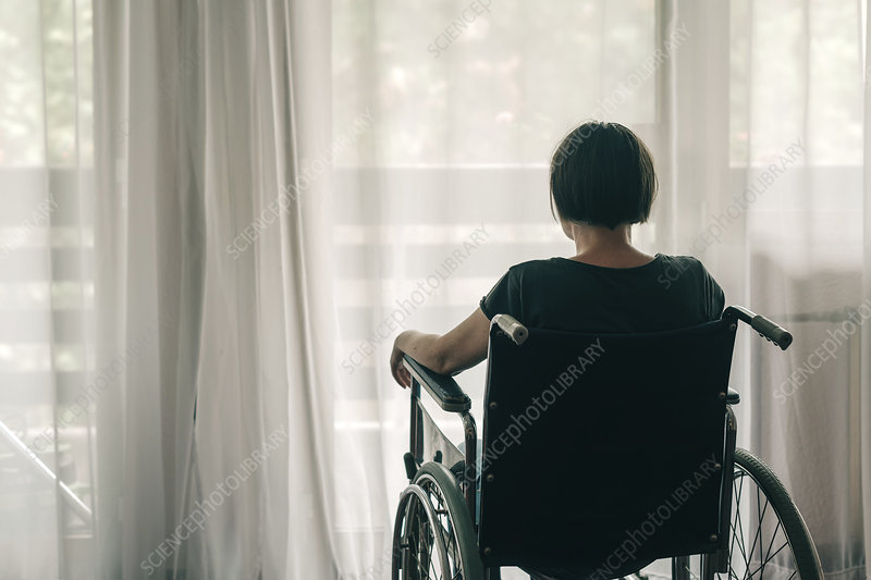 Depressed woman in wheelchair looking out the window