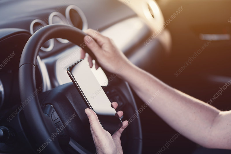 Woman texting on mobile phone in her car