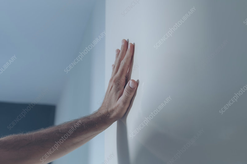 Male hand leaning on white interior door