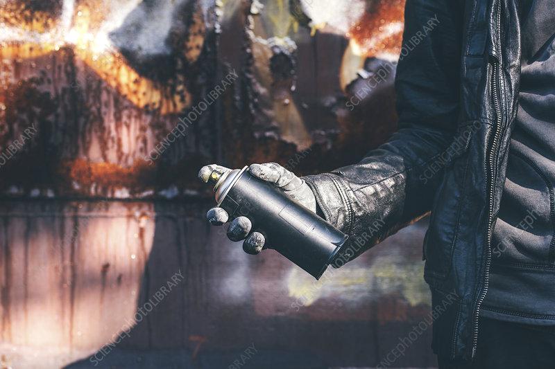 Man spray painting old train wagon with aerosol can