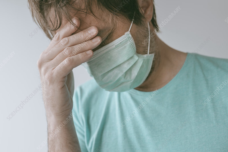 Man in mask with headache