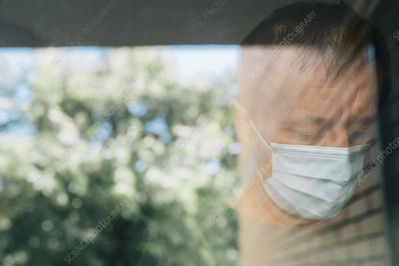 Worried man with protective face mask in self-isolation