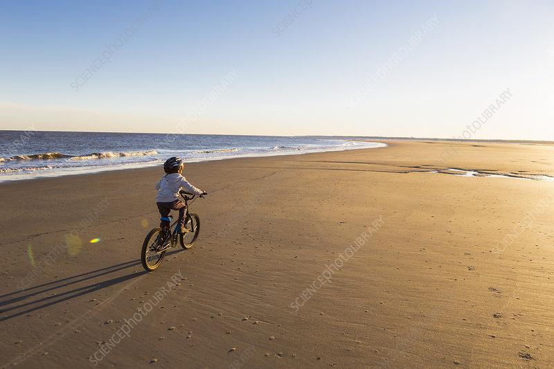 6 year old boy riding a bicycle on a beach