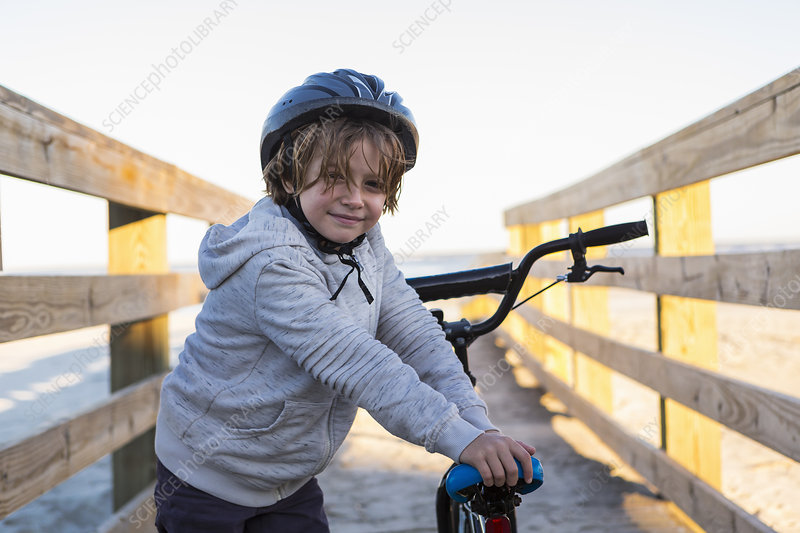 A boy on a bicycle, with helmet on a walkway