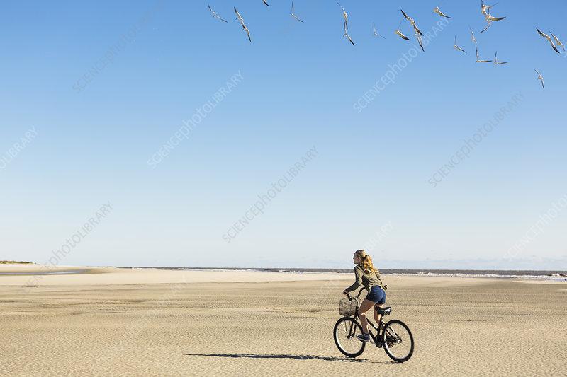 A teenage girl cycling on sand