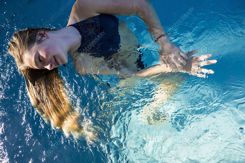 Teenage girl in a swimming pool, long hair fanning out