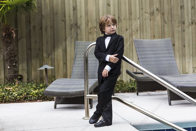 6 year old boy wearing formal attire standing by pool