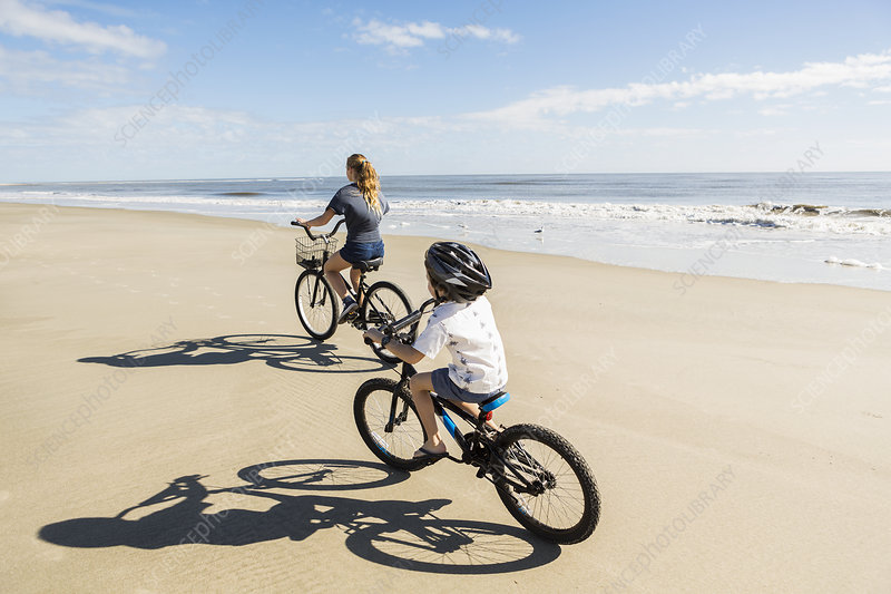 Children cycling on the sand by the water