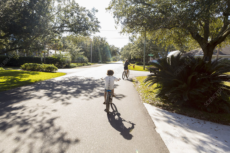 Teenager and her brother cycling on a suburban road