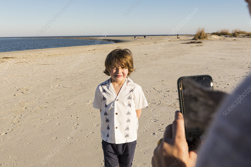 A six year old boy being photographed by his mother