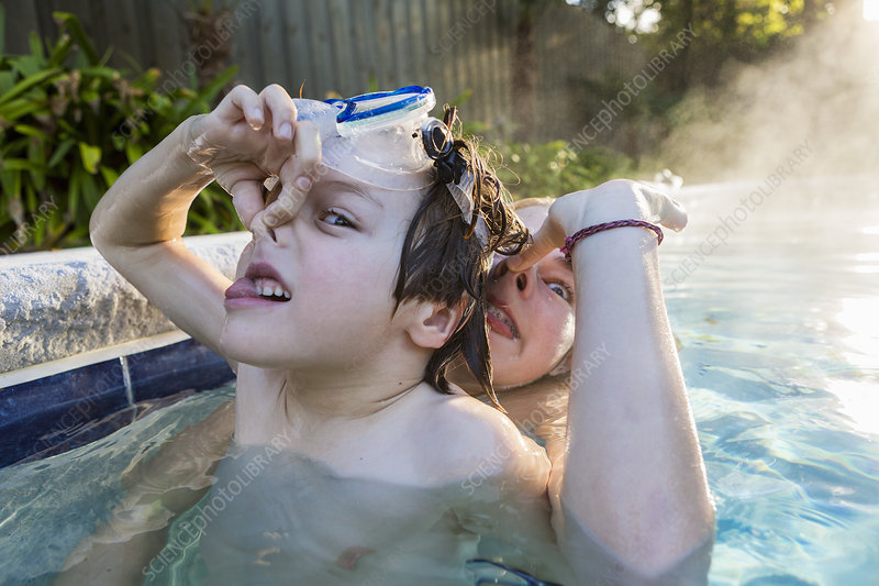 A boy in goggles and a teenage girl in a swimming pool