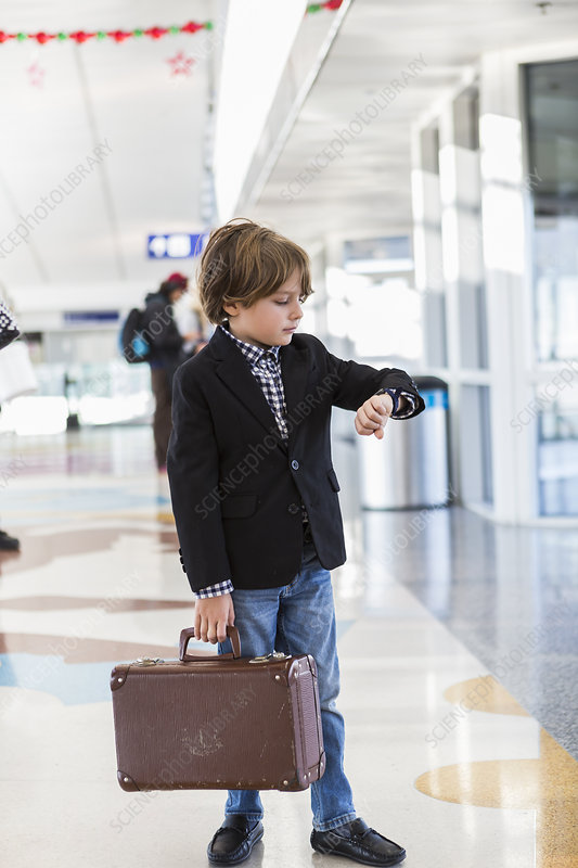 6 year old boy looking at his watch in airport