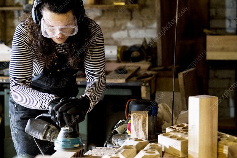 Woman standing in wood workshop, using sander