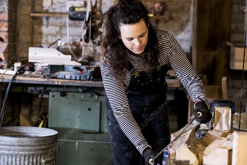 Woman in wood workshop using a plane on wood