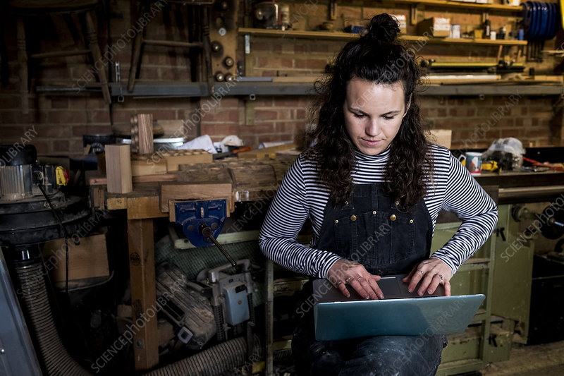 Woman in wood workshop, typing on laptop computer