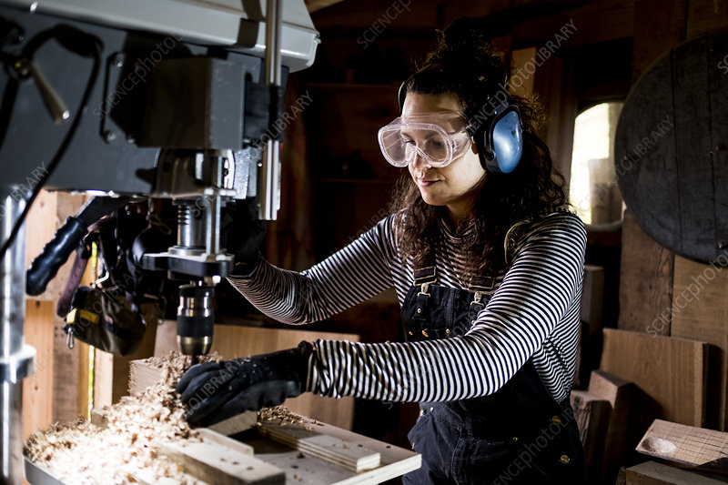 Woman in wood workshop using an electric drill