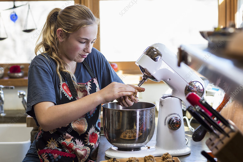 Thirteen year old girl using mixer in the kitchen