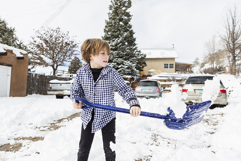 A six year old boy shovelling snow in driveway