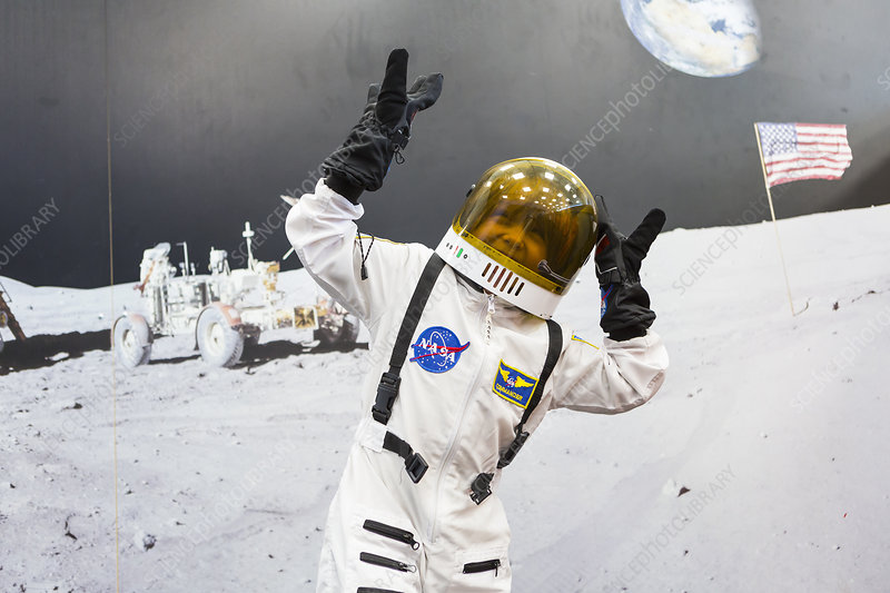 Boy wearing a space suit by image of the moon landing