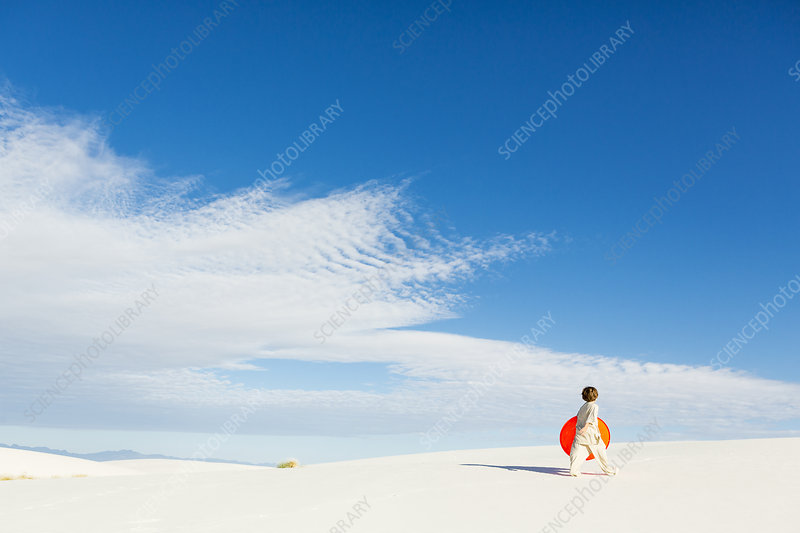 Boy carrying an orange sled in a white dune landscape