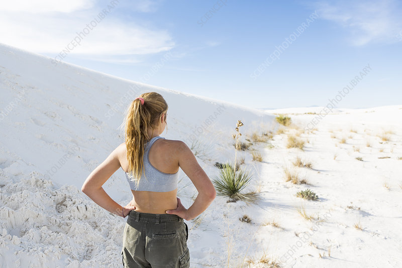 A teenage girl in an open landscape of white sand