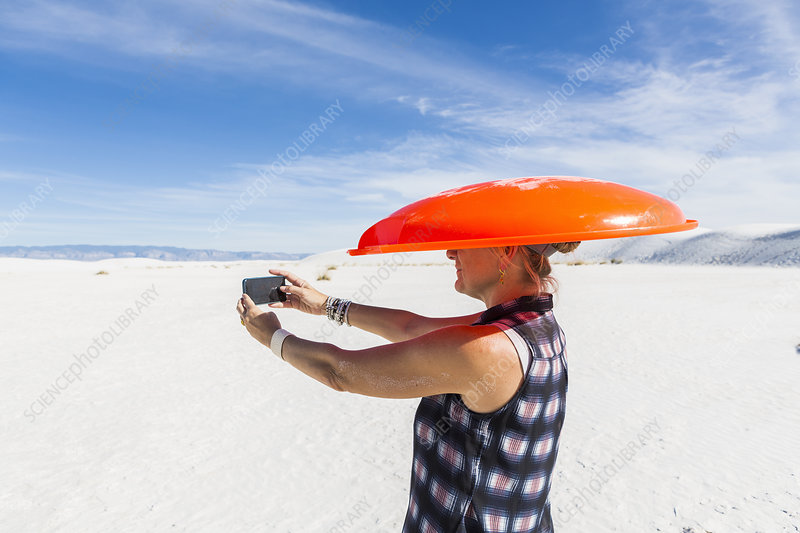 Woman carrying orange sled on her head, taking selfie