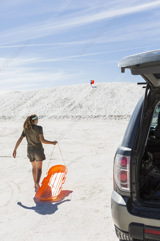 Teenage girl with sled in white sand dunes